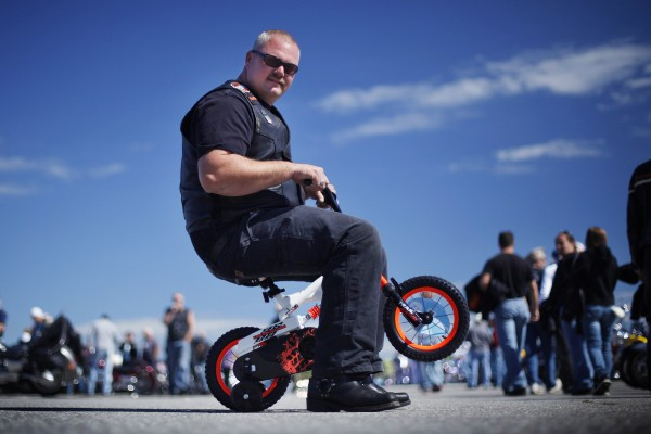 Biker Duayne Rollins pops a wheelie on the tiny bicycle he donated following the toy run. Rollins, an assistant fire chief in Solon, hopes to pass along his love of two-wheeled transportation to a needy child at Christmas.