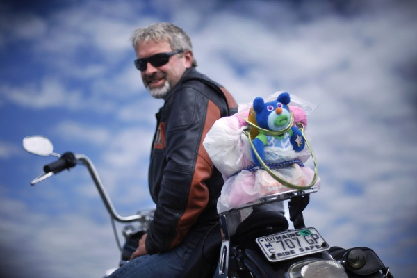 "Rob Frost poses on his bike with a ""sing-a-ma-jigs"" bear that he hopes will warm a kid's heart over the holidays."