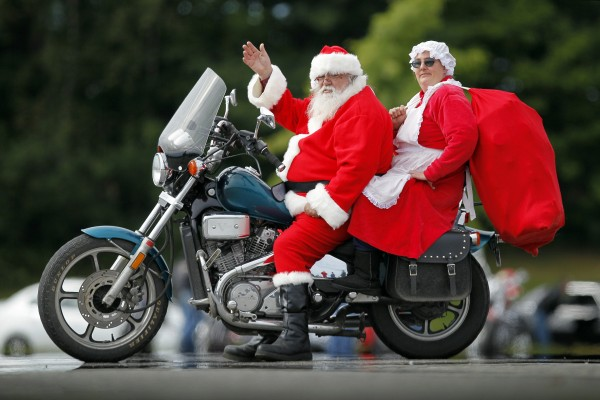 Santa Mark Rideout, with his helper, Pam McQueeney, gives a friendly wave before leaving on 30th annual toy run, Sunday in Augusta.