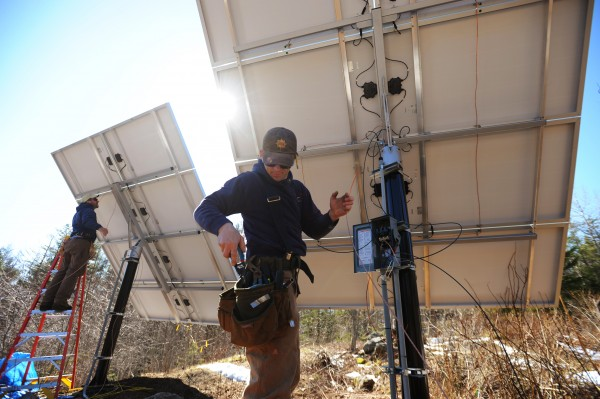 ReVision Energy employees Brian Bryne (left) and Eric Hertz finish the wiring on a pair of solar collectors at a Camden home in April.