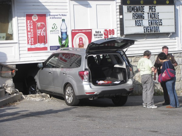 Sgt. Scott Kane with the Hancock County Sheriff's Office talks with two unidentified people involved in an SUV's crash in the Merrill & Hinckley store building in Blue Hill on Monday, Sept. 19, 2011. There were no serious injuries in the incident, which opened a hole in the building's basement.