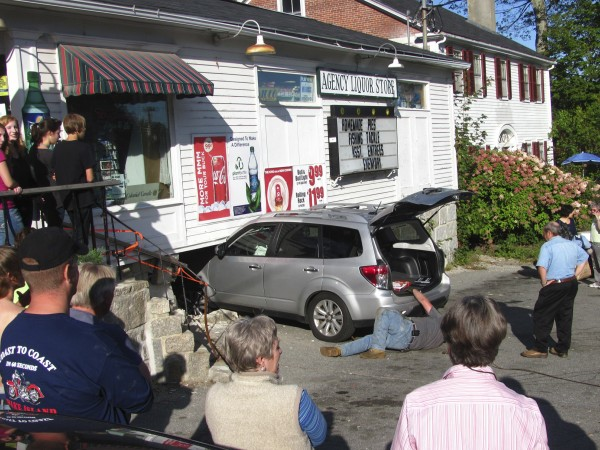 A crowd watches as a tow truck operator (on the ground) attaches a cable to the rear of an SUV that crashed through the wall of the Merrill & Hinkley market in Blue Hill on Monday, Sept. 19, 2011. Store owner John Bannister (standing at far right near the rear of the car) said this is at least the second time a car has smashed into the building.