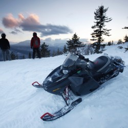 In this Jan. 28, 2011 photo, snowmobilers take in the scenery on a parcel of land sandwiched in between land owned by conservationist Roxanne Quimby in Township 5, Range 8, Maine.