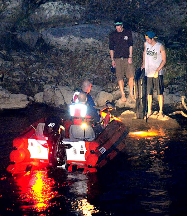 Rescuers approach two men trapped on rocks below the falls in the Androscoggin River on Wednesday night.