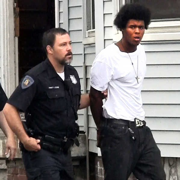 Lewiston police officer Robert Dionne leads Derrick McDuffy from an apartment on Walnut Street in Lewiston on Wednesday morning. McDuffy allegedly was involved in an armed robbery on Pierce Street.