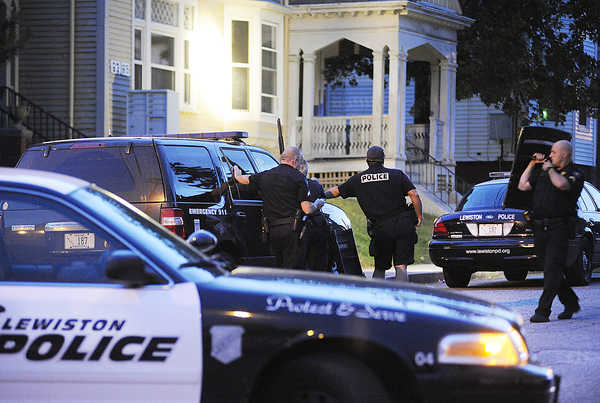 Lewiston police work at the scene of a standoff on Howe Street in Lewiston on Wednesday. Timothy B. Delisle, 37, of Auburn surrendered at about 8 p.m. and was arrested on several charges.