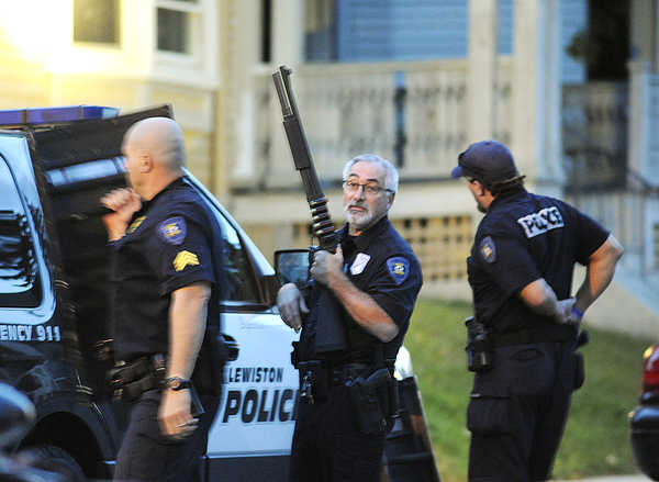 Lewiston police officers wait outside an apartment building on Howard Street where a suspect in a domestic fight was reportedly holed up with two handguns. Timothy B. Delisle, 37, of Auburn eventually surrendered and was arrested on a number of charges.