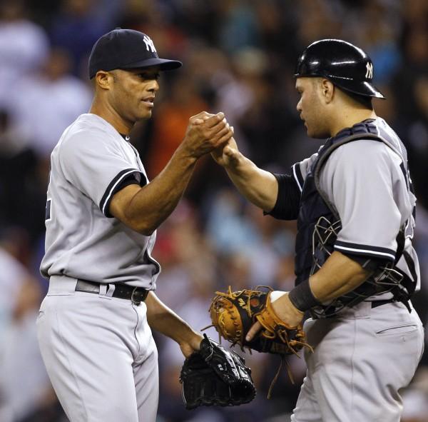 New York Yankees closer Mariano Rivera (left) is greeted by catcher Russell Martin after the team beat the Seattle Mariners on Tuesday, Sept. 13, 2011, in Seattle.