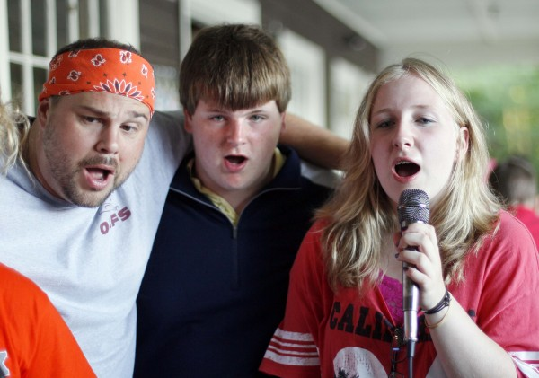 Simeon Welch, center, and his sister, Faith Welch, along with camp counselor,  Chuck Creteau, sing karaoke at Camp To Belong hosted by Camp Wigwam in South Waterford, Maine.