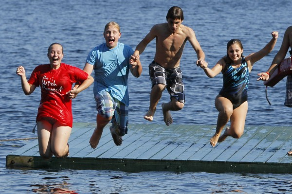 Campers, from left, Abbey Quill, her brother Duncan Dyer, Kyle Cummings, and his sister, Jasmine Coulter jump from a float into Bear Pond at Camp To Belong hosted by Camp Wigwam in South Waterford, Maine.
