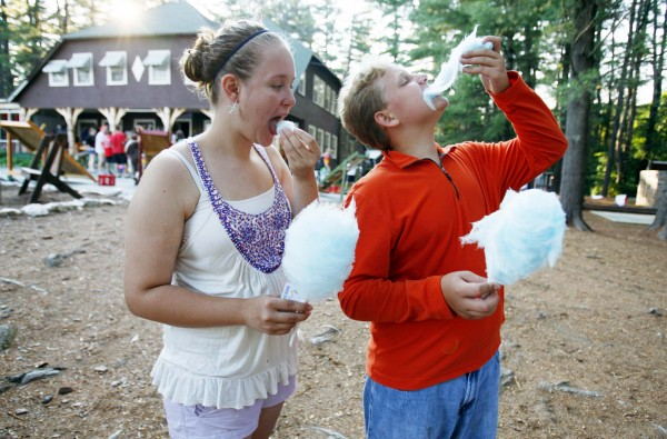 Abbey Quill and her brother Duncan Dyer eat cotton candy during carnival night at Camp To Belong hosted by Camp Wigwam in South Waterford, Maine.