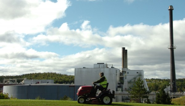 A town worker mows the Main Street median in front of the shuttered East Millinocket paper mill Friday morning, Sept. 16, 2011. This mill and the one in the Millinocket were due to be purchased by New Hampshire investor Cate Street Capital on Friday, Sept.16.