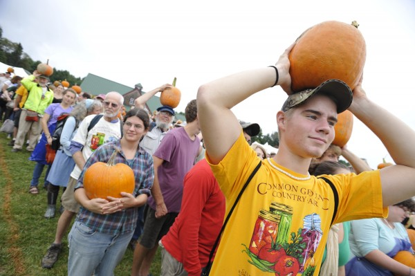 "Raising a locally grown organic pumpkin to the sky, Larry Crimi (foreground), 18 of Scranton, Pa., a conservation law enforcement major at Unity College, joined hundreds of others for the 350.org ""Moving Planet"" climate action event at the Common Ground Country Fair on Saturday afternoon, Sept. 24, 2011."