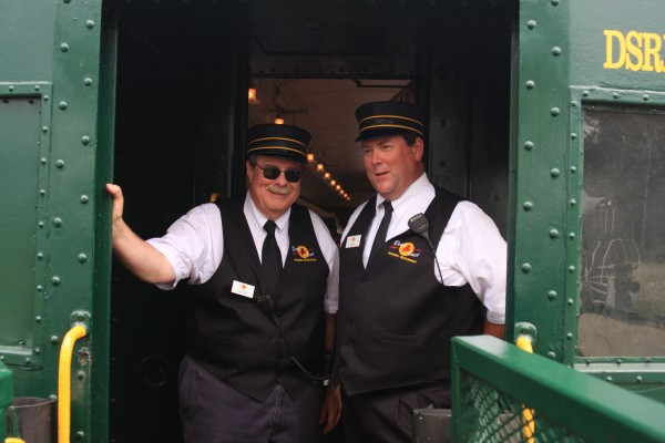 Volunteers George Thomas (left) and Gary Briggs greet Downeast Scenic Railroad passengers—young and old—as they board for a trip that through parts of Ellsworth, woodlands and marshes, past Osprey nests and beaver dams.