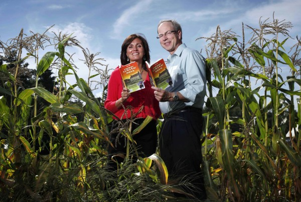 Farmers' Almanac editor Sondra Duncan and publisher Peter Geiger pose in a corn field with the 2012 edition of the almanac. The Almanac is reaching out to readers with an e-reader, mobile website for smartphones, and an app that's in the works.