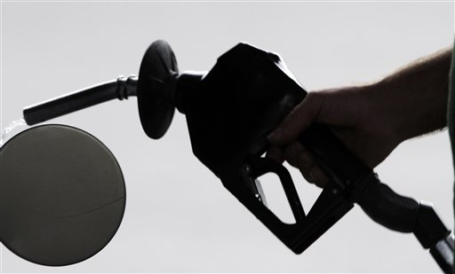 A motorist pulls the nozzle out of his gas tank after fueling his car at a station in Augusta, Maine, last year.