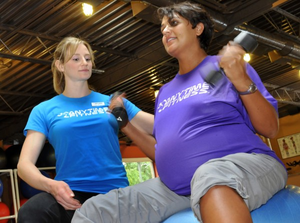 Anytime Fitness general manager and personal trainer Laura Burstein, left, keeps an eye on Leela Payne, who is pregnant, as she lifts weights.