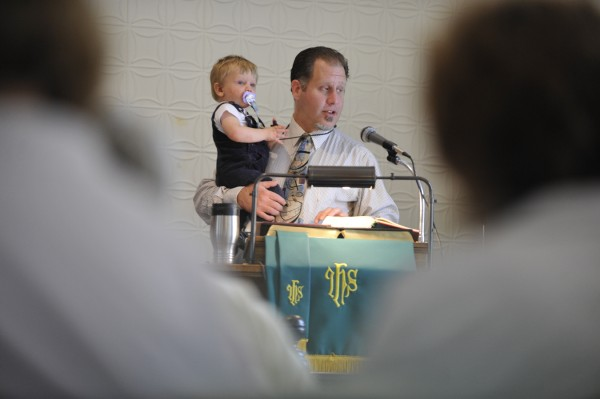 Holding his 17-month-old son, Alexander, Pastor Stephen MacLeod calls congregants to worship during Sunday's Labor Day weekend hymn sing at North Searsport United Methodist Church.