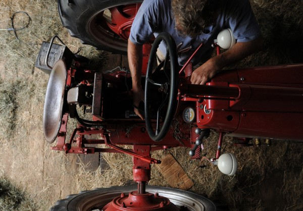 "Jeff Kelman jump-starts his 1956 Farmall tractor that he completely restored to working condition on Saturday, Sept. 10, 2011, before hooking a hay tedder to it and heading out into his sun-soaked hay fields. ""I keep my hand in farming because it's a benchmark to appreciate the maximum amount of work for the minimum amount of money,"" said Kelman."