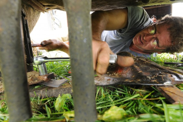With a socket wrench in one hand and steel lever in the other, Jeff Kelman changes cutter blades on his mower atachment before haying his fields on Friday, Sept. 9, 2011.