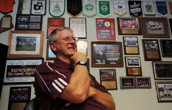 Ellsworth High School soccer coach Brian Higgins sits in the basement of his Surry home, surrounded by thepennants, plaques and framed photographs that speak to histhe accomplishments in his long career as a soccer coach.