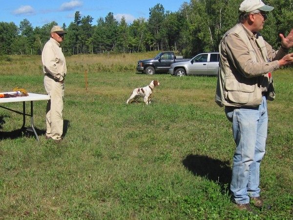 Bob Paucek of Buxton and CMBC member Gary Anderson of Stillwater explain the use of the whoa post. Pointing dogs are expected to hold their point until the hunter flushes and shoots the bird. There are several techniques for training this skill, including the whoa post, which Gary's dog Gunner is demonstrating. Gary is first vice president (field trials) of CMBC.