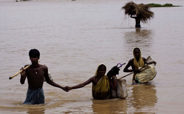Indian villagers wade through flood water near Gop village in Orissa's Puri district, about 35 kilometers (22 miles) from Bhubaneswar, India, Tuesday, Sept. 13, 2011. Heavy rains and flooding have killed at least 16 people in eastern India and left nearly 100,000 others homeless, an official said Monday.