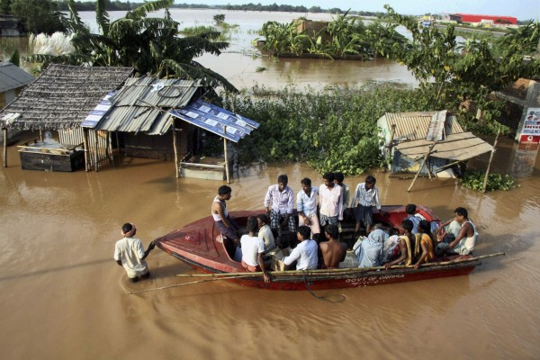 Indian villagers sit in a rescue boat in the flooded Rasulpur village in Orissa's Jajpur district, India, Monday, Sept. 26, 2011. Monsoon rains collapsed mud huts and riverbanks, flooding wide swaths of north and east India and killing at least 48 people over the weekend, officials said Monday.