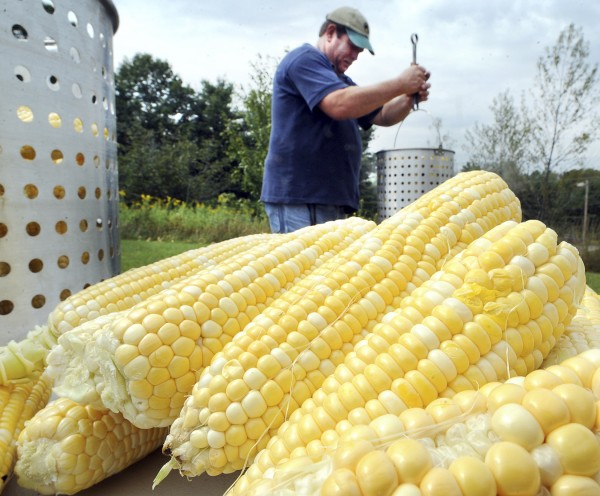Allan Shepard, president of IBEW Local 567, removes a batch of corn that is ready to be served as another is ready to go into boiling water outside his union hall on Goddard Road in Lewiston on Monday afternoon.