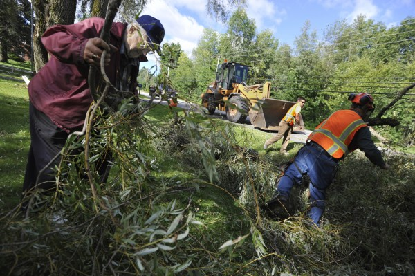 Dwinal Rideout (from left) helps Brewer Public Works employees Bobby Coombs and Casey Brooks as they remove tree debris from Rideout's front lawn off North Main Street in Brewer last month.