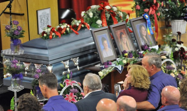 Ralph Bagley holds his wife Linda as they sit in front of the casket that holds their daughter, Amy Lake, and grandchildren, Cote and Monica, during their funeral Saturday, June 18, 2011, at Dexter Regional High School in Dexter.