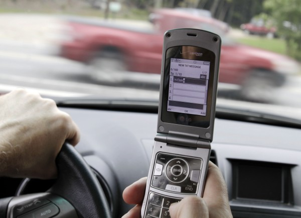 Joseph Dea, of West Hollywood, Calif., pauses as he texts while driving in a car in Brunswick, Maine, in this posed photo taken in September 2011. The texting ban is prominent among the scores of laws taking effect Wednesday, Sept. 28, the 90th day after the close of the 2011 regular session.