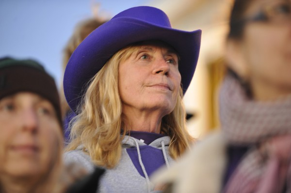 Donning a purple hat, P.J. McCluskey, wife of Hampden Academy football coach Harry McCluskey stands with other fans during the playing of the National Anthem before the start of Friday evening's home football game with Old Town High School.