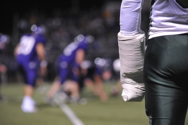 An Old Town player, sidelined with an arm injury, watches Coyote teammates battle the Hampden Broncos during Friday night's football game at Hampden.