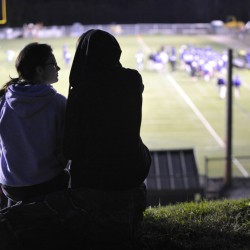 Hamdpen Academy senior Robert Palmer, right, of Winterport shares a quiet moment with his girlfriend amidst the din of Friday evening's football game with Old Town High School at Hampden Sept. 16, 2011.