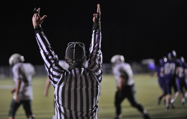A referee signals a Hampden Academy extra point during Friday evening's football game with Old Town High School at Hampden.