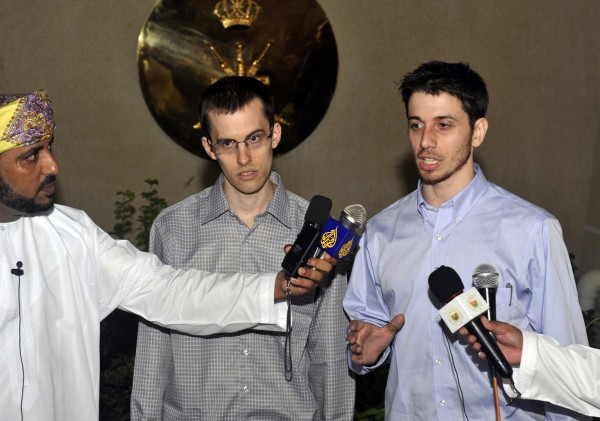 Freed American Shane Bauer, center, and Josh Fattal, right, talk to the media upon their arrival from Iran, in Muscat, Oman Wednesday, Sept. 21, 2011. After more than two years in Iranian custody, two Americans convicted as spies took their first steps toward home Wednesday as they bounded down from a private jet and into the arms of family for a joyful reunion in the Gulf state of Oman.