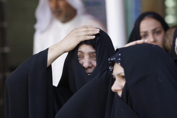 Mourners react during funeral of slain Shiite pilgrims at the Imam Hussein Shrine in the holy city of Karbala, 80 kilometers (50 miles) south of Baghdad, Iraq, Tuesday, Sept. 13, 2011. The victims were killed when gunmen forced their way onto a bus of traveling Shiite pilgrims Monday and shot all 22 men onboard as they traveled through western Iraq's remote desert on a trip to a holy shrine, security officials said.