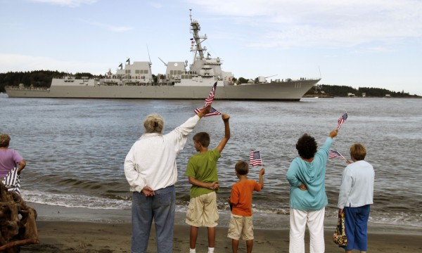 People greet the US Navy Destroyer, Spruance, as it passes Popham Beach in Phippsburg, Maine on its way from Bath Iron Works in Bath, Maine to her commissioning at Key West, Fla. in late October, on Thursday, Sept. 1, 2011.