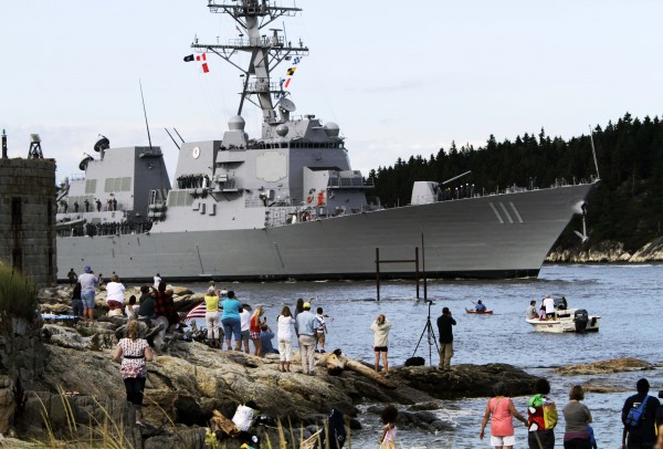 People greet the US Navy Destroyer, Spruance, as it passes Fort Popham in Phippsburg, Maine on its way from Bath Iron Works in Bath, Maine to her commissioning at Key West, Florida in late October, on Thursday, Sept. 1, 2011.