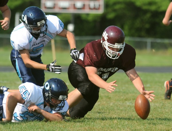 Nokomis High School's Josh Philbrook (right) recovers the ball after a fumble by the Oceanside Mariners' Garrett Burns (left top) during the first quarter of the game in Newport Saturday afternoon.