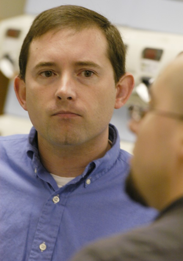 Reginald S. Gracie Jr. talks with pharmacy technician Nick Francis while giving a tour of the PIN Rx facility on Indian Island in November 2005.