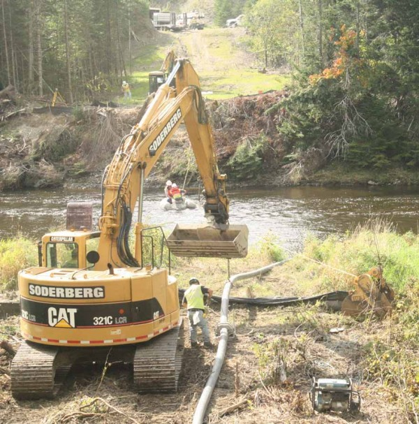 Construction workers begin efforts Tuesday afternoon to drill from one bank to the other under the Little Madawaska River in Caribou on Tuesday afternoon.