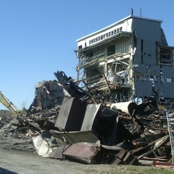 Approximately six weeks after the controlled implosion of the old heat plant at the former Loring Air Force Base in Limestone failed to bring down the entire structure, crews from Engineered Products in Portland pulled the last pieces down just before lunch time on Friday, Sept. 30, 2011. The steel, concrete and other material from the 64-year-old  building, pictured here roughly a day before it was completely dismantled, will be hauled away by Engineered Products. The company will cut and remove steel from the demolished building and sell the steel to help cover its demolition costs.