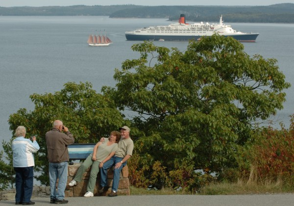 Joan and Ray Cripps (from left) take pictures of Mary Ray and Dale Crandall, all of Miramichi, New Brunswick, after stopping in 2007 on the Park Loop Road in Acadia National Park to watch the 151-foot-long, four-mast schooner Margaret Todd and the 963-foot-long Queen Elizabeth II. The cruise ship Veedam also was in Bar Harbor's port, bringing thousands of visitors to the tourist resort.