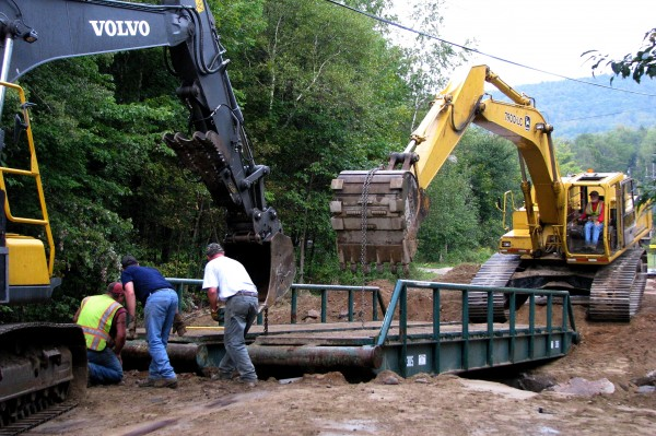 While installing a temporary bridge on Saturday morning at the Bean Brook washout on Swain Road, Rumford Public Works crewman Troy Duguay (left}, Mike Miller and Jim Nicols of Nicols Bros. Logging Inc. of Rumford check the alignment of bridge parts.