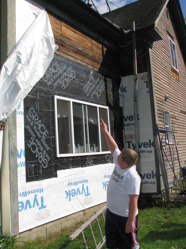 10-year-old Jeremy Record points toward the second-floor wall where Daniel Waite, 51, of Canton was 20 feet off the ground on a ladder applying siding when Record said he saw the ladder in the foreground suddenly slide off the side of the house, dumping Waite to the ground.