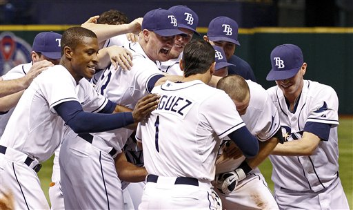 Tampa Bay Rays' Evan Longoria, second from right, is swarmed by teammates after his game-winning RBI-single in the 11th inning against the Boston Red Sox Saturday night, Sept. 10, 2011, in St. Petersburg, Fla. The Rays won 6-5.