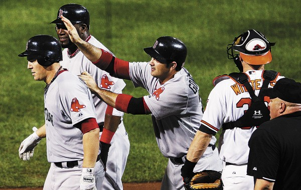 Boston Red Sox's Ryan Lavarnway, left, walks away from home plate with teammates David Ortiz, second from left, and Adrian Gonzalez after Lavarnway drove the two in on a home run in the fourth inning of a baseball game against the Baltimore Orioles on Tuesday night, Sept. 27, 2011, in Baltimore. At right is Orioles catcher Matt Wieters. Boston won 8-7.