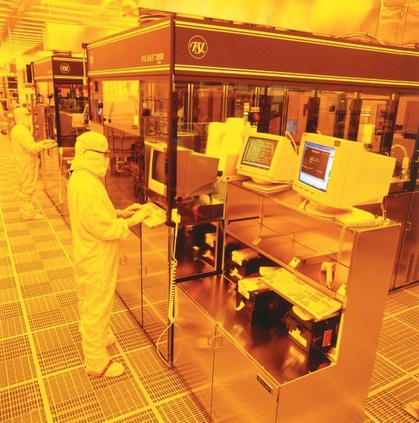 Workers process computer chip wafers at Fairchild's South Portland fabrication facility.
